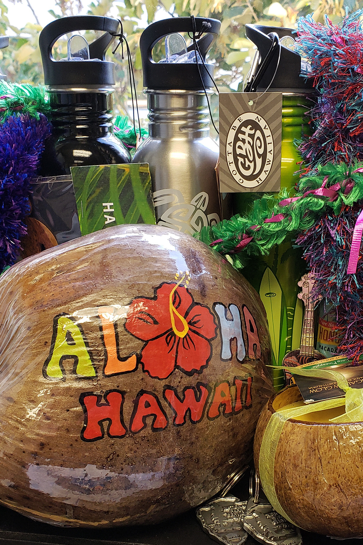 A collection of Hawaii-themed prizes given out in Descriptathon 5 (Aug. 27-29, 2019) are shown, amassed on a window ledge, with tropical foilage outside of the window and in the background. At the forefront of this collection is a coconut painted with two words: 1. ALOHA (in multiple colors; the A is yellow, the L is orange, the O is a red hibiscus bloom, the H is light blue, and the final A is Peach, all in capital letters). And, 2. HAWAII, also in all caps, but this word only is in red, and it is centered and right below the